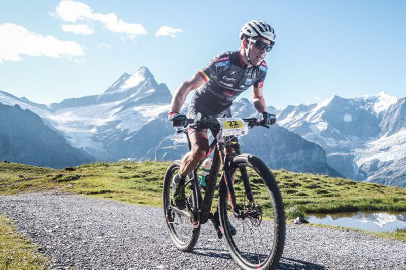 Ein Radsportler fährt über einen Trail vor dem Bergpanorama in der Nähe des Bodmi Berghotel in der Schweiz