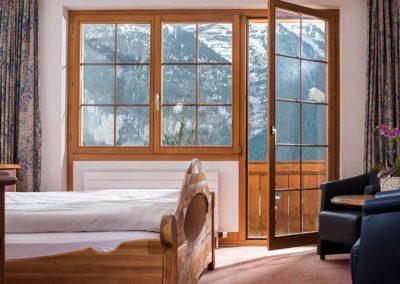 Ein Holzbett in einem gemütlich eingerichtetem Zimmer mit Balkon und Blick auf die Eiger Nordwand im Bodmi Erholungshotel
