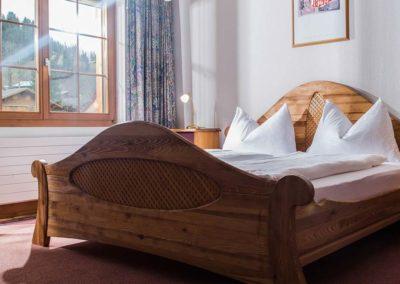 Ein Holzbett in einem Familienzimmer Bodmi Erholungshotel
