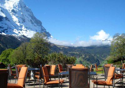 Die Aussenterasse des Bodmi Romantikhotel mit Tischen und Stühlen, die eine herrliche Aussicht auf den schneebedeckten Gipfel des Eiger bietet