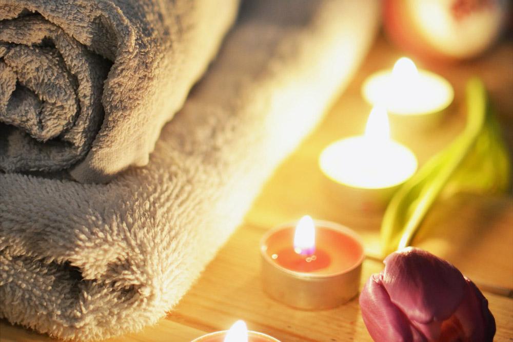 Teelichter neben einem Stapel Handtücher und einer Tulpe - Wellnessurlaub auf Schweizer Art Bodmi Hotel