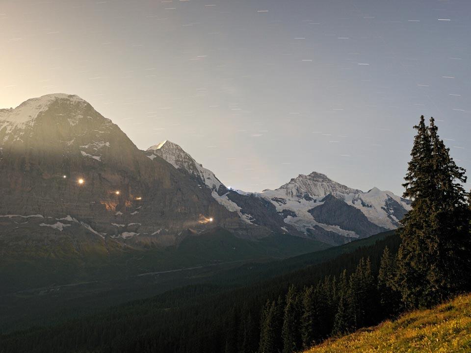 Eine Wiese neben dem Berg Eiger in der Nähe des Bodmi Wanderhotel in der Schweiz wird von der untergehenden Sonne in ein gelbes Licht getaucht