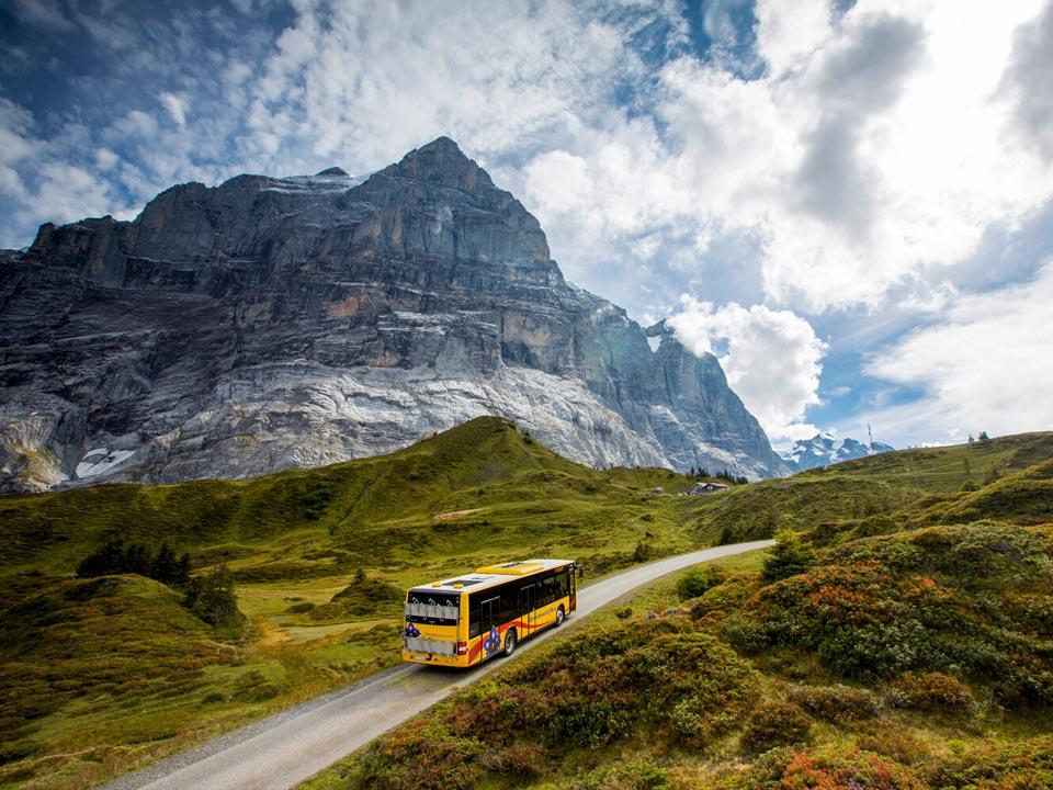 Ein gelber Bus fährt über den Bergpass auf den Großen Scheidegg, in der Nähe des Bodmi Berghotel in der Schweiz