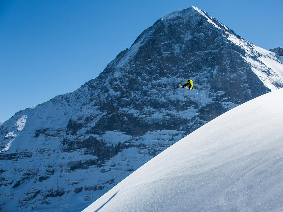 Ein Snowboarder vollführt einen Sprung vor dem Gipfel eines Bergs im Skigebiet Grindelwald First in der Jungfrauregion