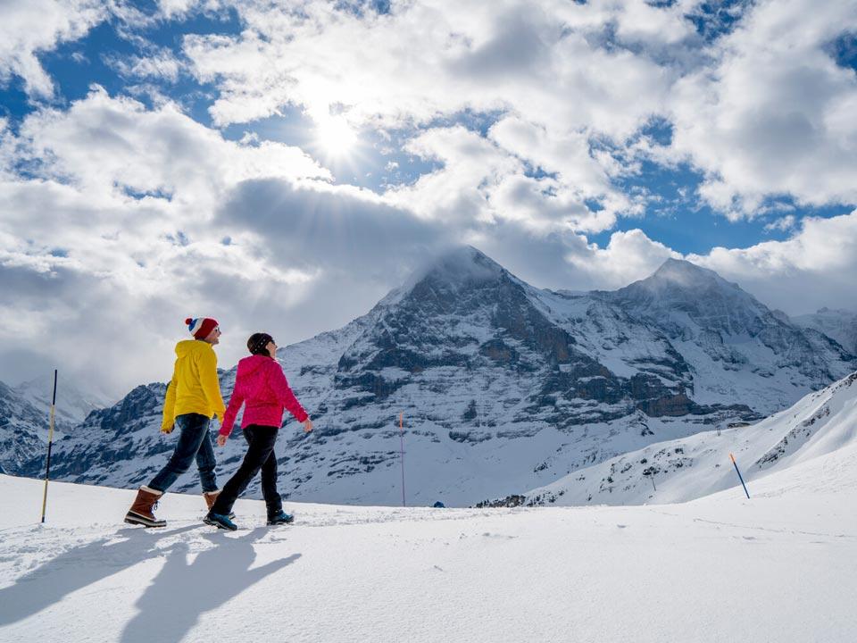 Zwei Personen in Wanderbekleidung wandern im Schnee über einen Weg unterhalb des Eiger Nordwand Gipfels in der Nähe des Bodmi Berghotel in der Schweiz