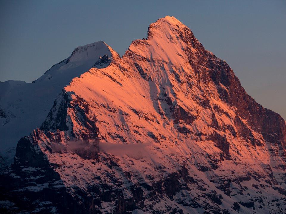 Der schneebedeckte Gipfel der Eiger Nordwand in der Nähe des Bodmi Wanderhotel in der Schweiz wird in ein rotes Abendlicht getaucht