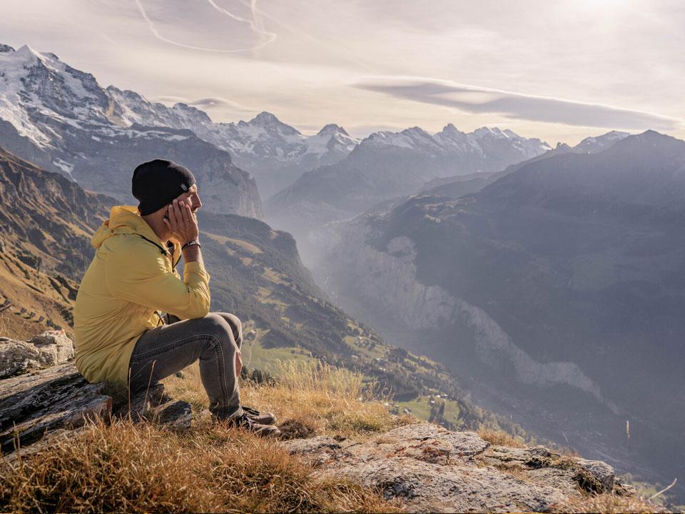 Ein junger Mann mit gelber Jacke sitzt am Hang des Männlichen in der Jungfrau Region in der Nähe des Bodmi Berghotels in der Schweiz und blickt ins Tal