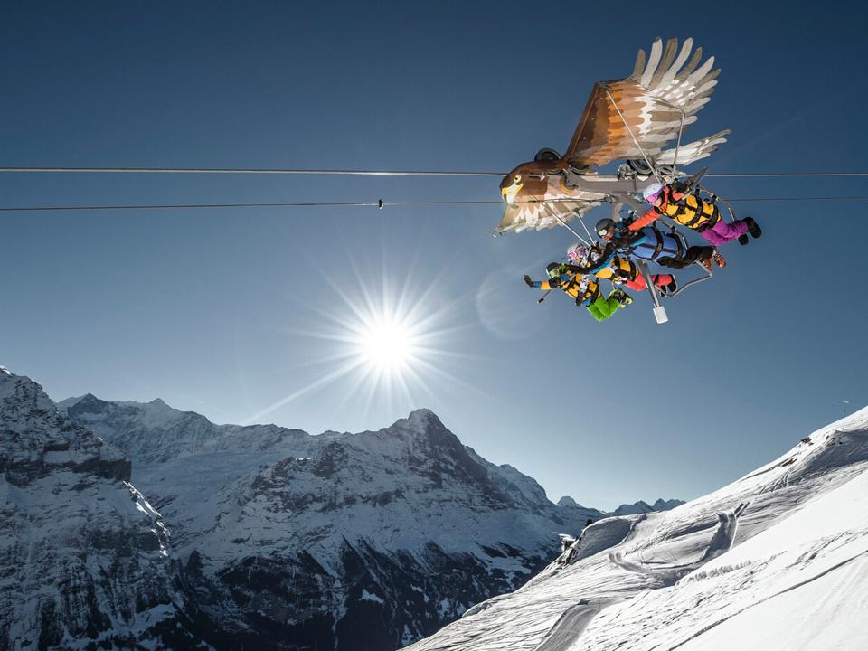 Mehrere Personen gleiten an einer Leine am Himmel entlang, als Teil eines Erlebnis- und Wanderurlaub in der Schweiz