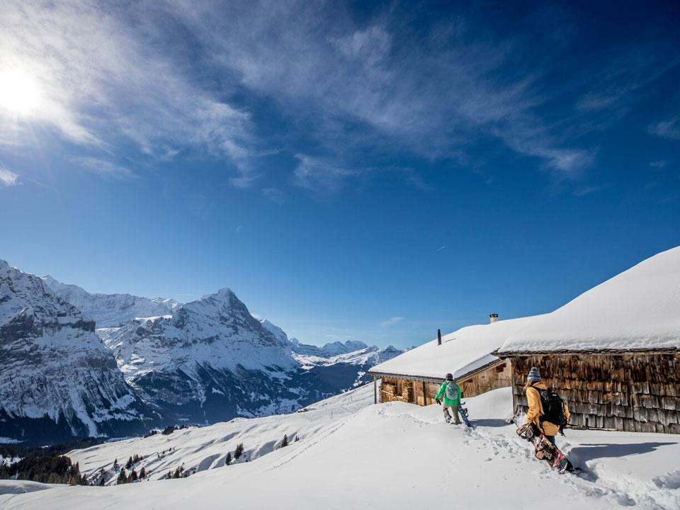 Zwei verschneite Holzhütten stehen auf einem Berg im Skigebiet Grindelwald, zwei Snowboarden ziehen ihre Ausrüstung zu den Hütten