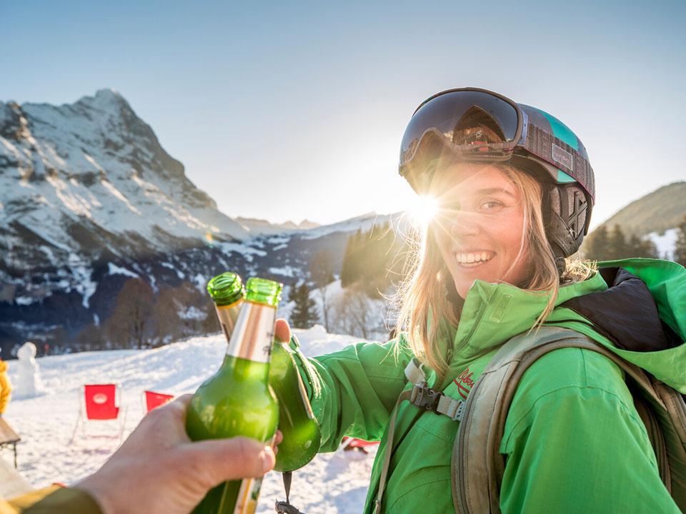 Eine junge Frau mit Skihelm stößt im Skigebiet Grindelwald mit einer Person mit Bier an