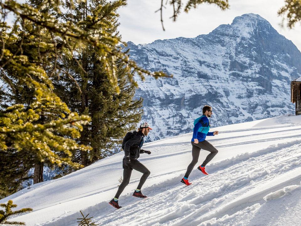 Zwei junge Männer in Sportbekleidung betreiben Trail-Running auf der verschneiten Piste des Skigebiet Grindelwald