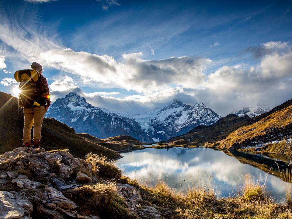 Eine Person mit Wanderrucksack steht während des Sonnenaufgangs vor einem Bergsee auf dem Eiger, in der Nähe vom Bodmi Berghotel Grindelwald