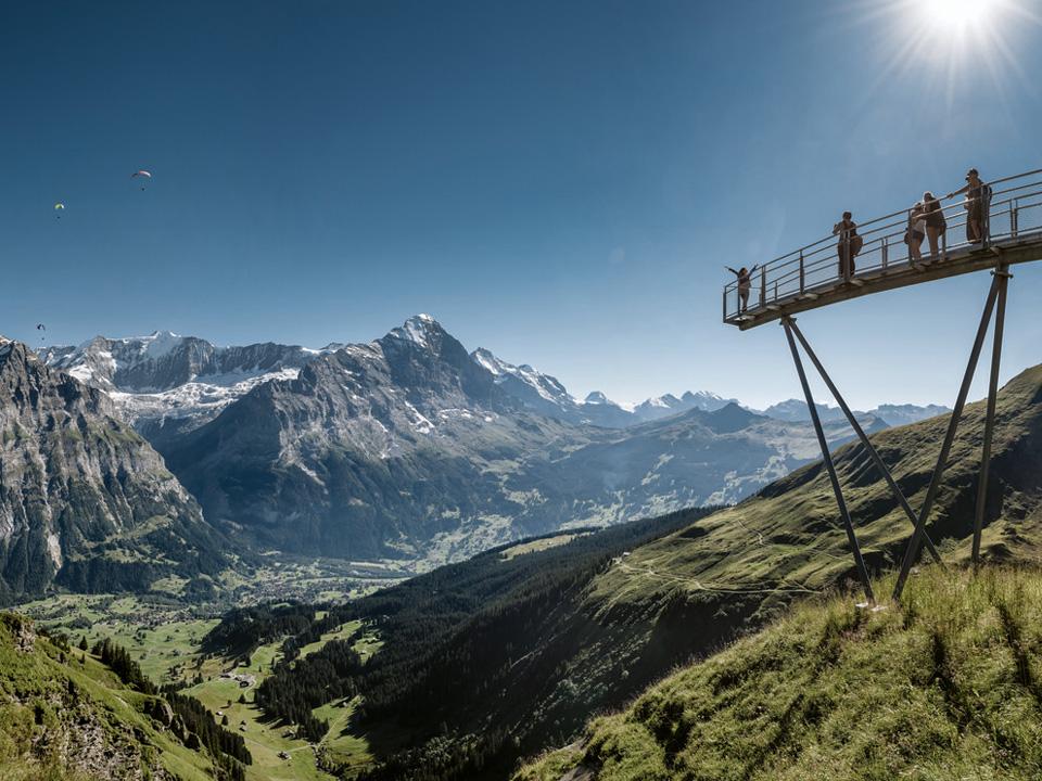 Mehrere Personen stehen auf einer Aussichtsplattform mit Aussicht auf das Faulhorn, die auf einem der vielen Wanderwege in Grindelwald liegt