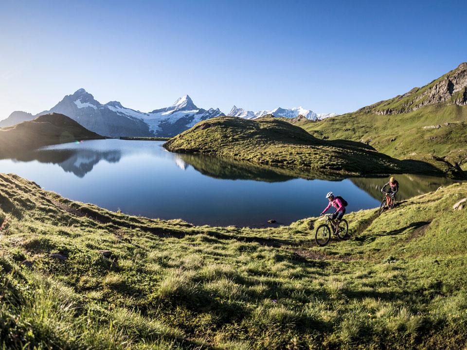 Zwei Radfahrer umrunden den Bachalpsee in der Nähe des Bodmi Berghotel in Grindelwald