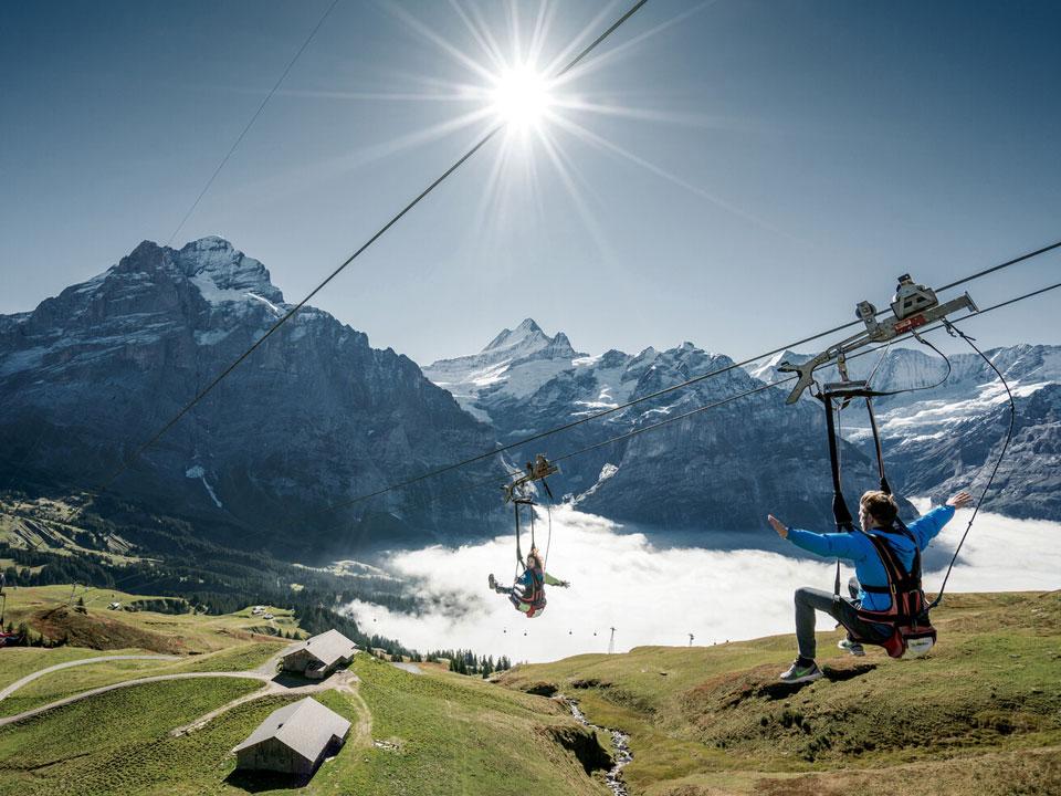 Personen gleiten vor der atemberaubenden Bergkulisse an einer Seilbahn ins Tal, im Rahmen eines Erlebnis und Wanderurlaub in der Schweiz