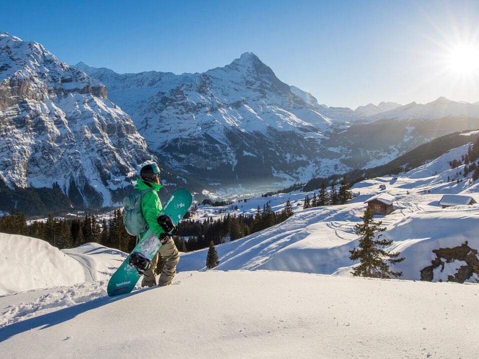 Ein grün gekleideter Snowboarder steht auf einem Hang im Skigebiet Grindelwald und blickt auf die Berge im Hintergrund