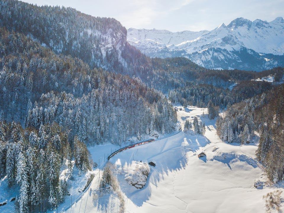 Ein roter Zug fährt durch die verschneite Berglandschaft, die sich für einen Winterurlaub in Grindelwald anbietet