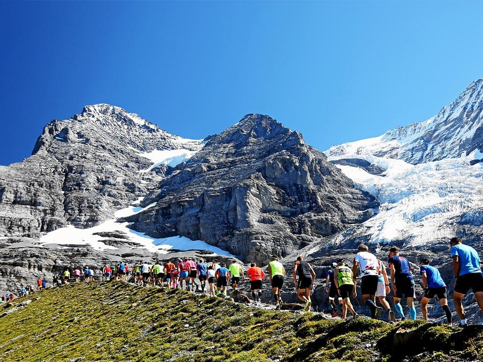 Zahlreiche Sportler steigen einen Berg im Rahmen des Jungfrau Marathon hinauf. Der Marathon findet in auf einem der zahlreichen Wanderwege in Grindelwald statt
