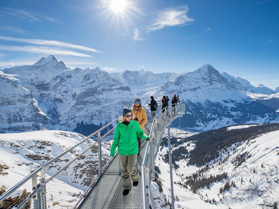 Mehrere Personen laufen über einen Skywalk mit Ausblick über das Jungfraujoch in der Jungfrauregion