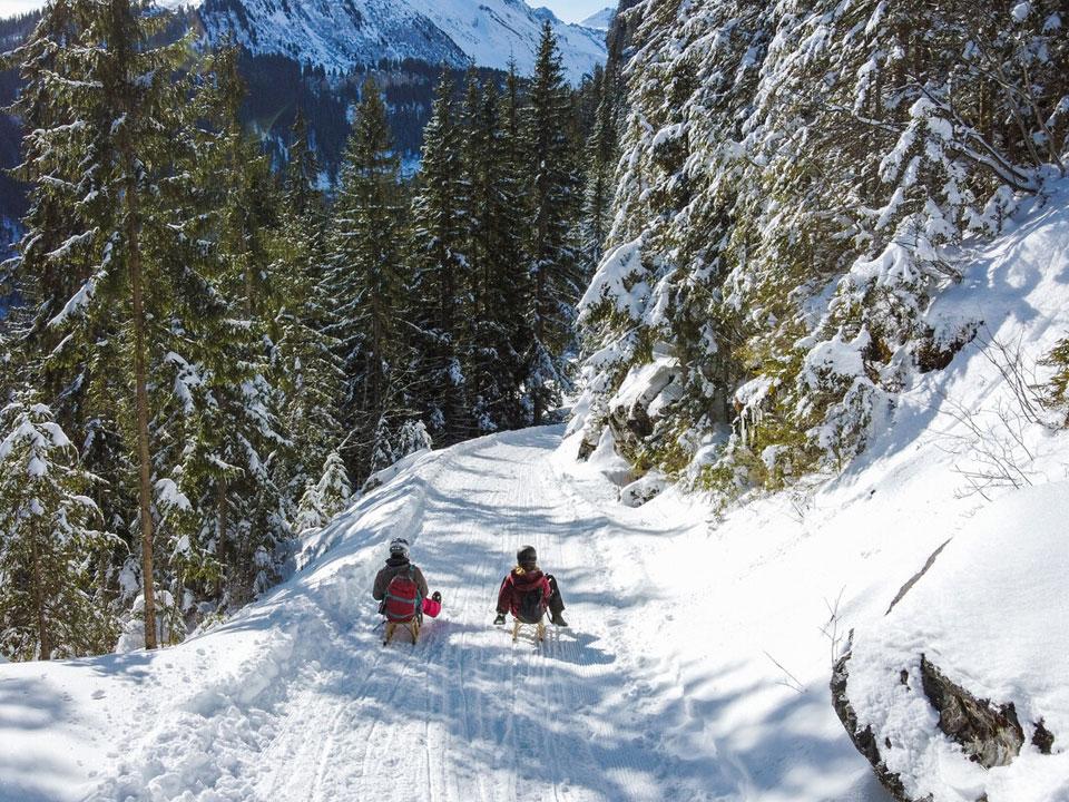 Zwei Personen auf einem verschneiten Weg beim Schlittenfahren in Grindelwald