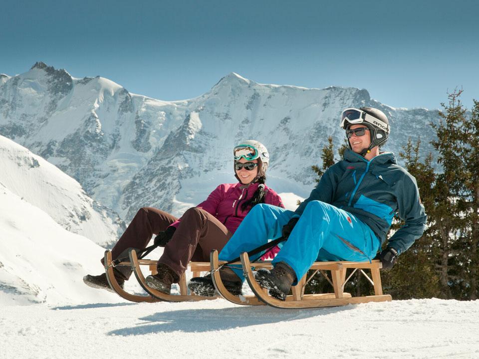 Ein Mann und eine Frau in Skibekleidung sitzen im Skigebiet Grindelwald auf Holzschlitten
