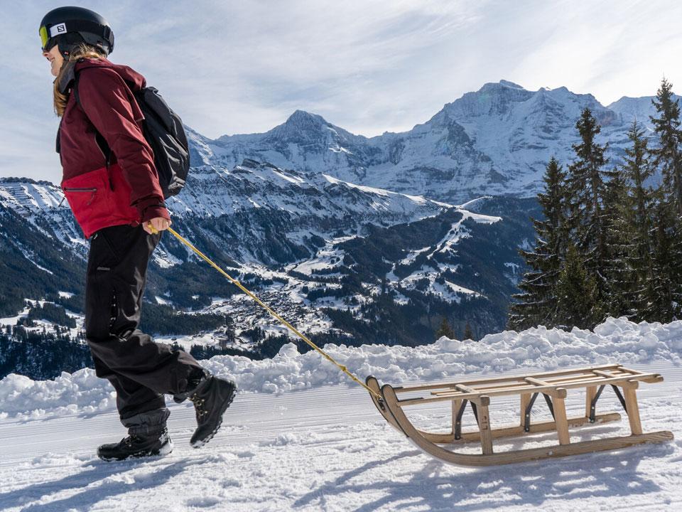 Eine junge Frau in Skibekleidung zieht einen Schlitten nach dem Schlittenfahren in Grindelwald über einen schneebedeckten Weg