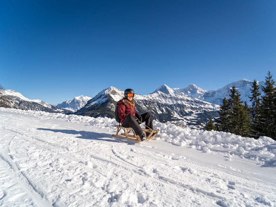 Eine junge Frau in Skibekleidung auf einem verschneiten Weg beim Schlittenfahren in der Schweiz