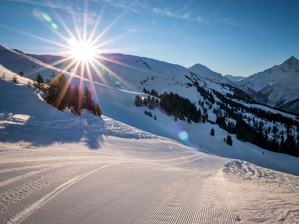 Die Skipiste Hasliberg im Skigebiet Grindelwald wird von einem Sonnenuntergang angstrahlt