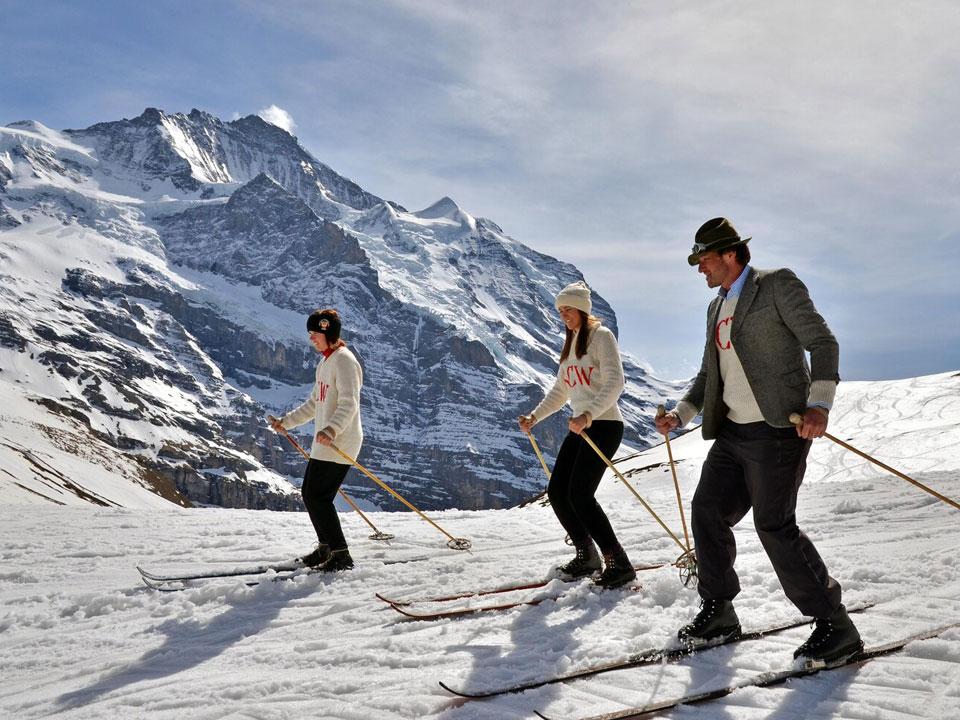Drei Personen stehen mit Skiern auf einer Skipiste im Skigebiet Wengen