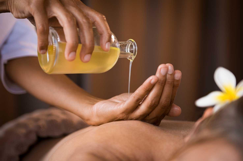 Eine Person gibt Massageöl auf ihre Hand, in Vorbereitung auf eine Massage im Bodmi Wellnesshotel in der Schweiz