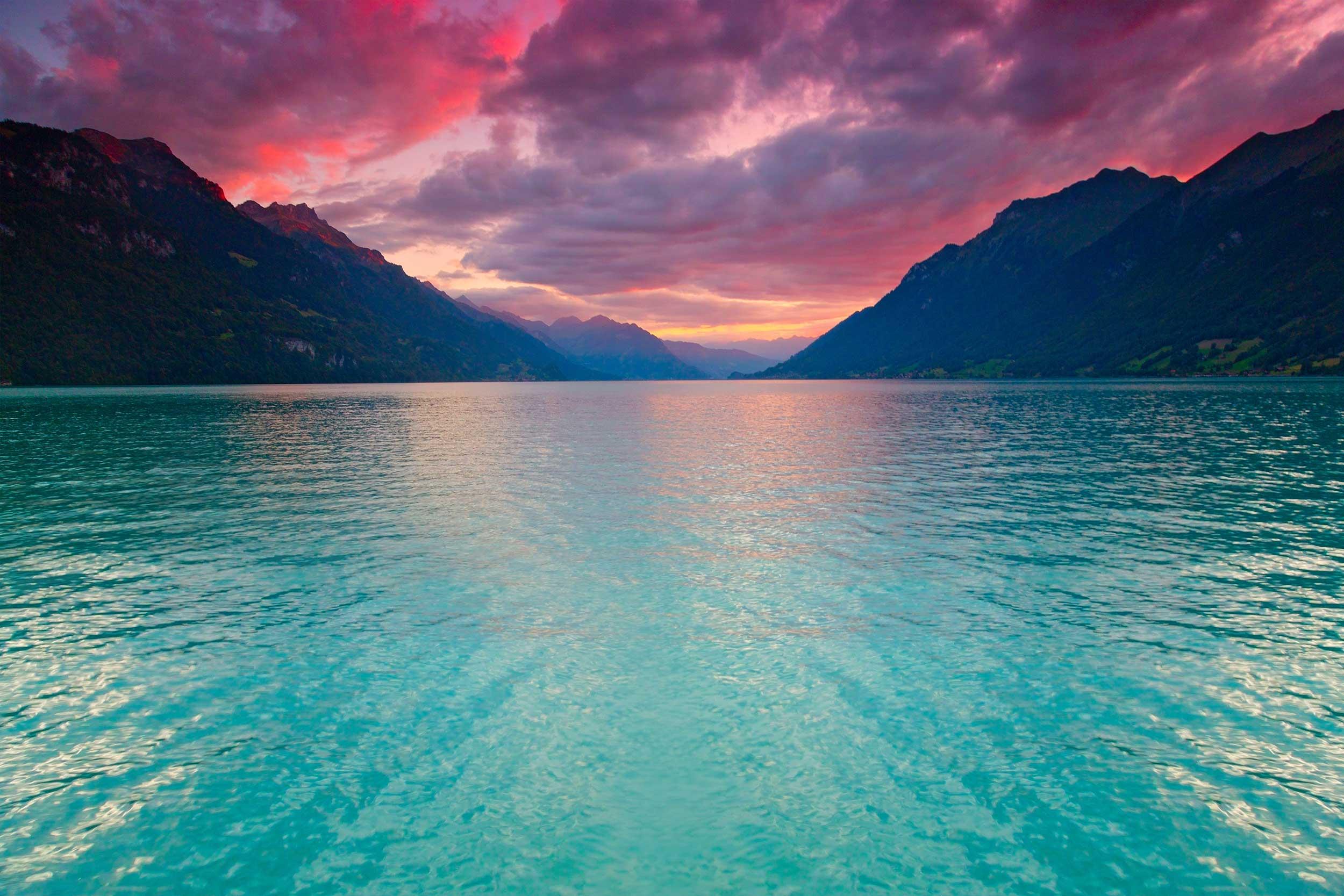 Das türkis-blaue Wasser des Brienzersee schimmert im Abendrot vor einer Bergkette, in der Nähe des Erholungshotel Bodmi