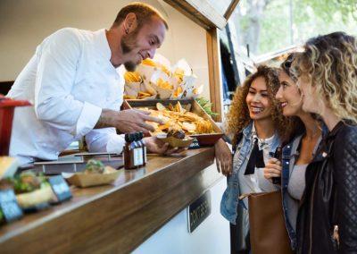 Drei Frauen stehen vor einem einem authentischen und modernen Angebot an Fingerfood-Snacks aus dem Outdoor-Imbisswagen des Bodmi Hotels, der für Schweizer Genussmomente sorgt