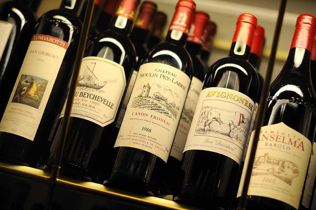 Verschiedene Weinflaschen in einem beleuchteten Regal sorgen für Genussmomente im Bodmi Hotel