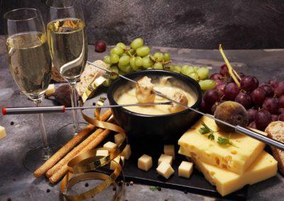 Eine Auswahl an Trauben, Sekt und geschmolzener Käse in einer schwarzen Schale sorgen beim Fondue-Abend für Schweizer Genussmomente im Bodmi Hotel