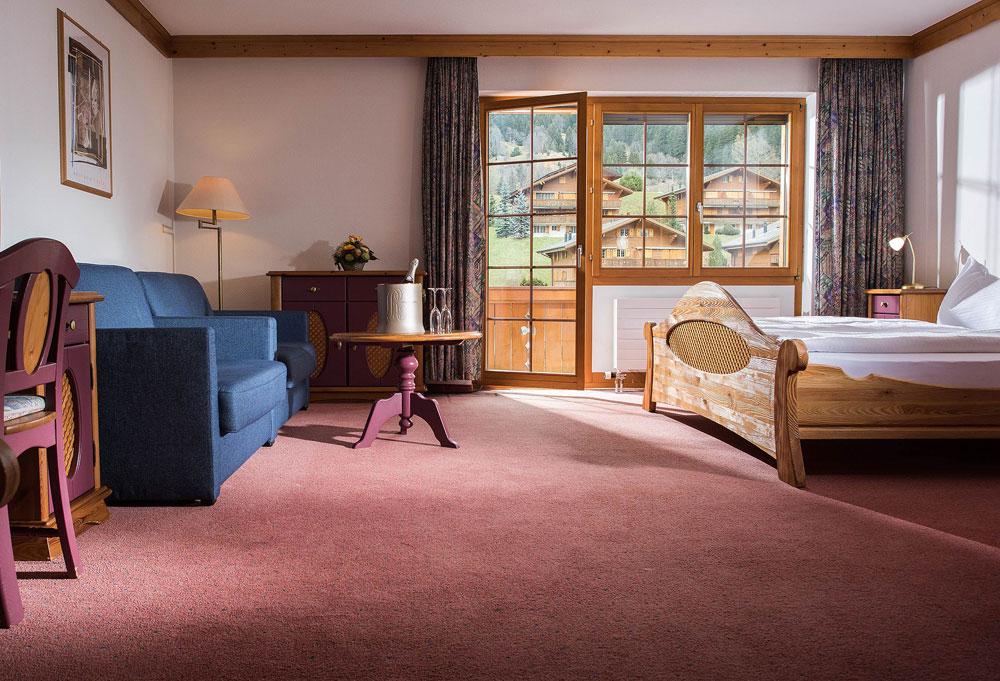 Blick in das Familienzimmer mit gemütlichem Holzbett im Hotel Bodmi